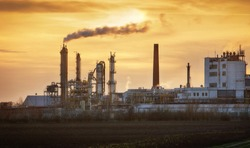 Factory pipe polluting air, smoke from chimneys against sun, environmental problems, ecological theme, industry scene