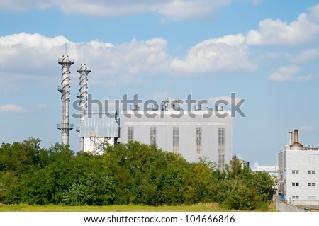 Factory pipes and building on a background of the blue sky with clouds