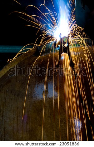Factory welder making his daily job. Vertical.