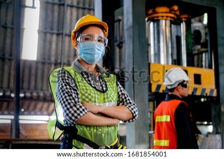 Factory woman worker or technician with hygienic mask stand with confident action with her co-worker engineer in workplace during concern about covid pandemic in people affect industrial business. Stockfoto ©
