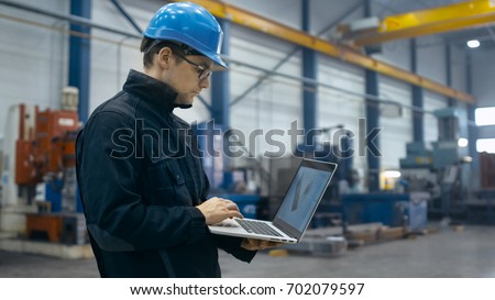 Factory worker in a hard hat is using a laptop computer with an engineering software.