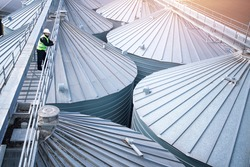 Factory worker in protective clothes walking on grain elevator and observing silos rooftops. Industrial food and grain storage.
