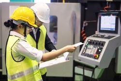 Factory worker inspector or manager discuss inspection report on paper for internal audit at high technology machine. Quality assurance (QA) for manufacturing industry.