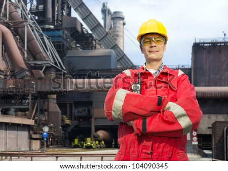 Factory worker posing in front of a blast furnace, wearing safety gear, including a hard hat, goggles and fire retardant coveralls