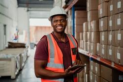 Factory worker smiling holding digital tablet organising parcels in warehouse