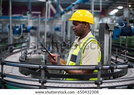 Factory worker using a digital tablet near the production line in factory