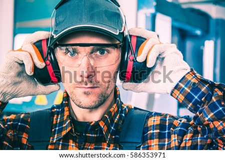 Factory Worker Wearing Hearing Protectors and Protective Goggles.