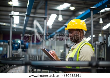 Factory worker writing on the clipboard in factory
