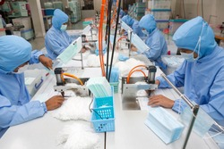 Factory workers are producing masks for protection against viruses.