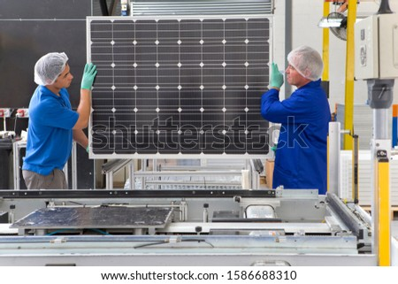 Factory workers lifting new solar panel from production line
