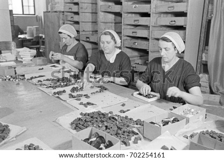 Factory workers putting chocolate candy into boxes