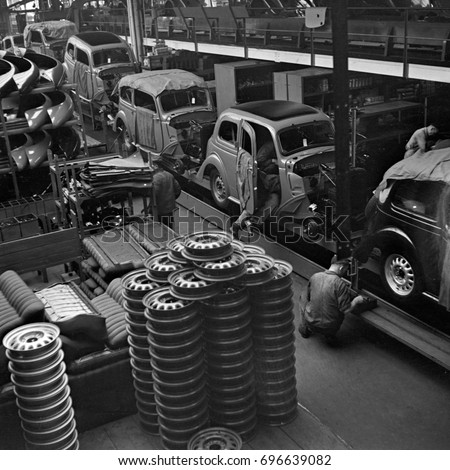 Factory workers putting hub cabs on cars on assembly line