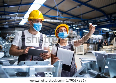 Factory workers with face masks protected against corona virus doing quality control of production in factory. People working during COVID-19 pandemic.