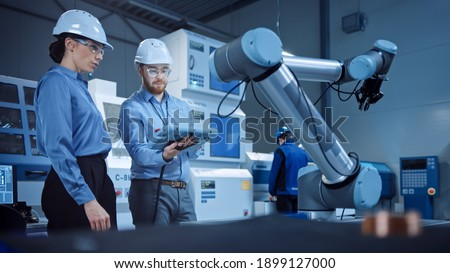 Factory Workshop: Professional Female Engineer, Male Machinery Operator Use Industrial Digital Tablet Computer to Work and Program Robot Arm for Production Line. High-Tech Facility with CNC Machines