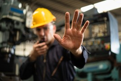 Factory zone restricts access industrial area, Industrial worker in factory site gesture keep out while communicating with a walkie talkie, Concept Disallow warning, working profession, call police.