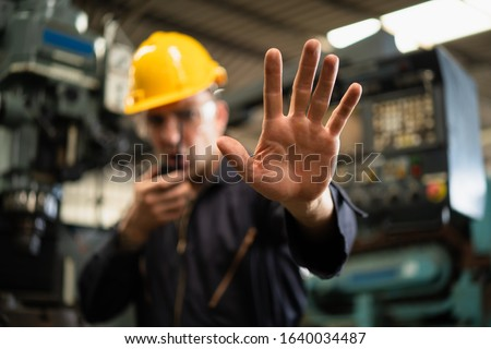 Factory zone restricts access industrial area, Industrial worker in factory site gesture keep out while communicating with a walkie talkie, Concept Disallow warning, working profession, call police. Stock photo ©