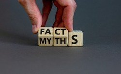 Facts or myths symbol. Businessman hand turns cubes and changes the word 'myths' to 'facts'. Beautiful grey background, copy space. Business and facts or myths concept.