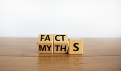 Facts or myths symbol. Turned cubes and changed the word 'myths' to 'facts'. Beautiful wooden table, white background, copy space. Business and facts or myths concept.