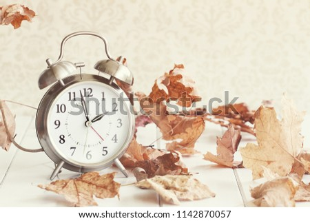 Faded Alarm clock in colorful autumn leaves against a retro background with shallow depth of field. Daylight savings time concept.