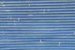 Faded blue weathered garage door of abandoned industrial warehouse