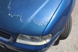 Faded car paint - peeling paint surface in a 15 year old compact blue car.