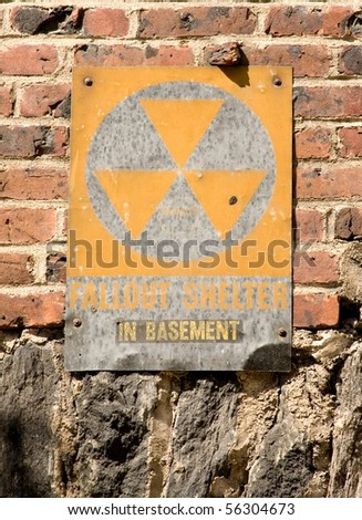 Faded fallout shelter sign on brick