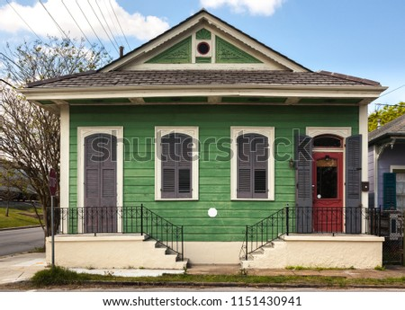 Faded green paint on a quaint duplex in the Bywater neighborhood of New Orleans, Louisiana.