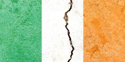 Faded Ireland national flag icon isolated on weathered cracked concrete wall background, abstract vintage Irish political conflicts concept pattern texture wallpaper