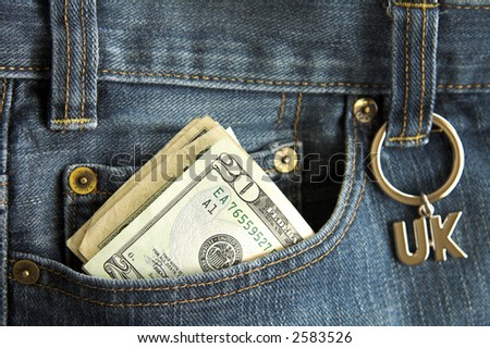 Faded jeans with a UK key ring on belt loop and dollar notes in pocket