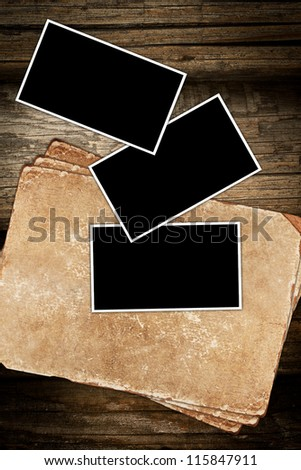 Faded old paper and photo frames on a wooden background