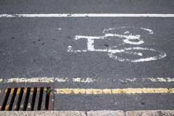 Faded painted cycle lane symbol on road