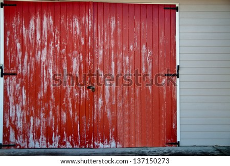 Faded red barn door with black latches on a white building