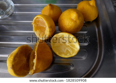 Faded squeezed lemons on counter top, Remaining peels of lemon after squeezing, top view. Food ingredient concept, Residue of food background. It can be used for cleaning. The waste of fruit peels. Foto stock ©