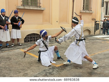 """FAENZA, ITALY - NOVEMBER 6: indians Sikh in traditional costume performing a knife duel with a old fighting weapon at """"Fiera di San Rocco"""" that hosts historical recalling on November 6, 2011 in Faenza"""