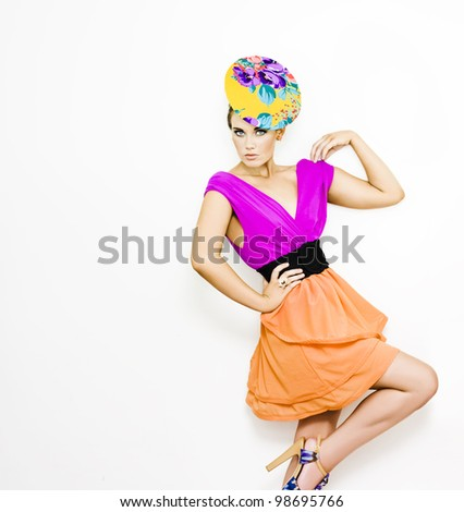 fahion model wearing bright purple blouse, orange skirt and floral hat on a white background