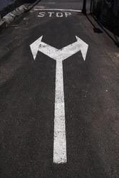 Fahrbahnmarkierung STOP und Richtungspfeile, nur rechts- und linksabbiegen erlaubt
