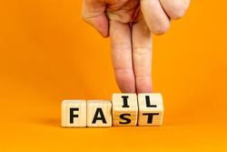 Fail fast symbol. Businessman turns wooden cubes with words 'fail fast' on beautiful orange background, copy space. Business and fail fast concept.