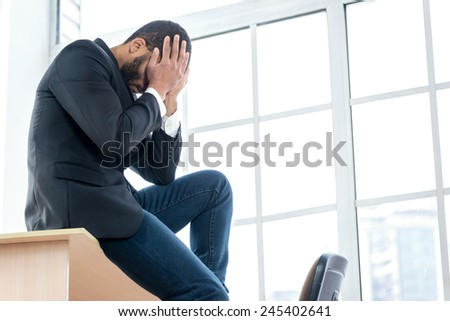 Failure in business. Sad businessman sitting at desk in office until his head bowed down holding his hands behind his head. Businessman dressed in formal wear