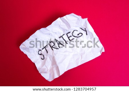 Failure startup strategy concept. Word Strategy written on Crumpled paper on red background #1283704957
