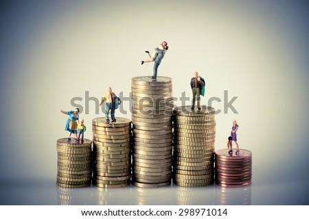 Faily budget concept. Miniature family on coins pile. Macro photo