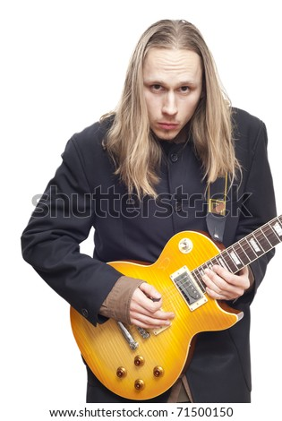 Fair haired guitar player with black suit looking into camera