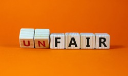 Fair or unfair symbol. Turned a cube and changes words 'unfair' to 'fair'. Beautiful orange background. Business and fair or unfair concept.
