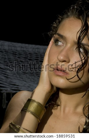 Fair skinned model with wet hair and gold bracelets looking away from the camera?
