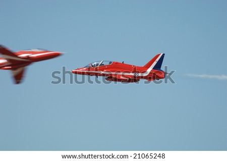 FAIRFORD, UK - JULY 16: RAF Red Arrows squadron solos perform a crossing manuever at the Royal International Air Tattoo on July 16, 2005 in Fairford, UK.
