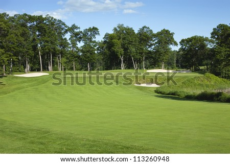 Fairway and green of a golf course on a sunny afternoon