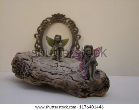 Fairy Angel sitting on an old weathered piece of driftwood with a vintage ornate frame in the background  #1176401446