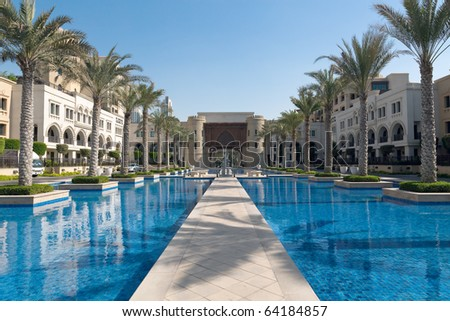 Fairy arabian palace. Alley between two ponds surrounded by rows of palms. - stock photo
