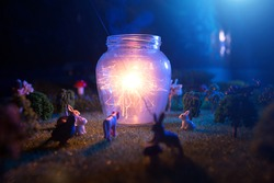 Fairy forest. The animals gathered to see a miracle lamp shining from sparklers. Fictional fairytale macro world.