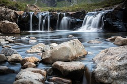 Fairy pools waterfalls surrounded by mountains during a cloudy day on the Isle of Skye in Scotland