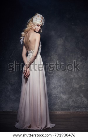 Fairy Princess in this beautiful long evening gown and the crown on his head. Perfect figure of a woman, slender body, beautiful makeup. Back of the girl, graceful hands